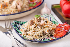 Traditional uzbek pilaf (plov) with tomatoes and red onion Royalty Free Stock Photography