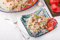 Traditional uzbek pilaf (plov) with tomatoes and red onion Royalty Free Stock Photo