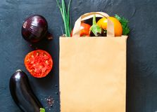 Traditional vegetables in paper bag on dark background, shopping in supermarket, concept of healthy diet, copy space. Closeup royalty free stock photos