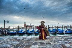 Venetian masked model from the Venice Carnival 2015 with Gondolas in the background near Plaza San Marco, Venezia, Italy. Traditional venetian carnival, dramatic stock image
