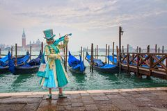 Venetian masked model from the Venice Carnival 2015 with Gondolas in the background near Plaza San Marco, Venezia, Italy royalty free stock photography