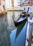 Gondola with shadow. Traditional venetian gondola on the small canal water Royalty Free Stock Image