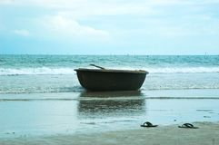 A Vietnamese basket-boat on a beach, resting near a pair of shoes on the sand. Stock Photo