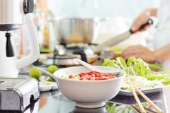 Traditional Vietnamese beef noodle soup Pho Bo. With garnish of leaves of cilantro, Asian basil and bean sprouts on kitchen table. Young woman is cooking in Stock Photography