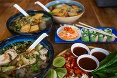 Traditional Vietnamese food. Soups, rolls and fresh herbs. Plates on a wooden surface. stock photo