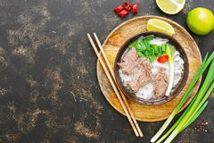 Traditional Vietnamese pho soup with rice noodles and beef in a bowl on a wooden tray. Dark background, top view, copy space.