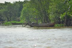 Vietnamese wooden fishing boats moored in the jungle by a muddy river. Stock Photography