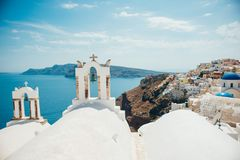 Traditional view of the sea and island with two white bell towers on Santorini Royalty Free Stock Photo
