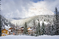 Traditional Village at the Foot of a Woody Mountain Covered in Snow Royalty Free Stock Image
