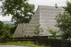 Traditional village historical building of Western Ukraine, where the roof is covered with wooden tiles. Skansen Uzhhorod. Ukraine.  Royalty Free Stock Image