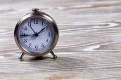 Traditional vintage alarm clock on white wooden boards Royalty Free Stock Photo