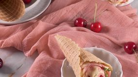 Traditional waffle cones with ice cream. And cherry fruits on marble stone surface stock video footage