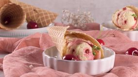 Traditional waffle cones with ice cream. And cherry fruits on marble stone surface stock video
