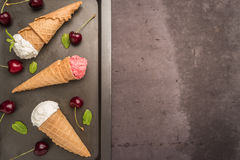Traditional waffle cones for ice cream on wooden table. Traditional waffle cones for ice cream on background. Cherry icecream and fresh cherries. Cones filled stock photo