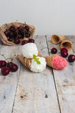 Traditional waffle cones for ice cream on wooden table. Cherry ice cream and fresh cherries. Cones filled with ice cream stock photo