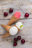 Traditional waffle cones for ice cream on wooden table. Cherry ice cream and fresh cherries. Cones filled with ice cream royalty free stock photo