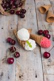Traditional waffle cones for ice cream on wooden table. Cherry ice cream and fresh cherries. Cones filled with ice cream stock photography