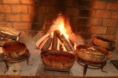 Traditional way of cooking. By open fire in clay pot on tripod Stock Images