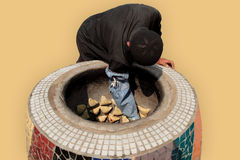 The traditional way of cooking samsa. Samsa is getting baked in the traditional central asian owen - tandir - isolated on netural background Royalty Free Stock Photo