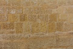 Traditional weathered stone wall background in Malta. Traditional weathered limestone wall facade background in Malta Stock Photos