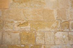 Traditional weathered stone wall background in Malta. Traditional weathered limestone wall facade background in Malta Stock Image