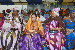 Traditional Wedding. Abidjan, Ivory Coast - February 26, 2015: young married woman sitting surrounded by her two godmothers. young woman sitting tattooed hands Royalty Free Stock Image
