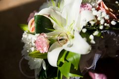 The wedding bouquet with gold ring. A traditional wedding bouquet of liliea and roses with gold ring inside closeup Royalty Free Stock Photography