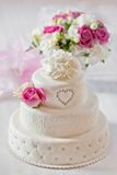 Traditional wedding cake with rose flowers. Traditional wedding cake and bridal bouquet Stock Images