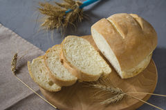 Traditional wheat bread. On the wooden board. Nearby lies napkin and wheat spikelets Stock Photography