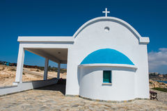 Traditional white chapel with a blue roof on the seaside. Agioi Stock Photos