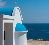 Traditional white chapel with a blue roof on the seaside. Agioi Royalty Free Stock Photography