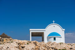 Traditional white chapel with a blue roof on the seaside. Agioi Royalty Free Stock Images