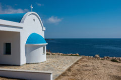 Traditional white chapel with a blue roof on the seaside. Agioi Stock Photography