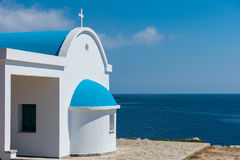Traditional white chapel with a blue roof on the seaside. Agioi Stock Image