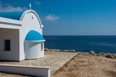 Traditional white chapel with a blue roof on the seaside. Agioi. Traditional Greek white church with a blue roof on the seaside. Agioi Anargyroi orthodox Stock Image