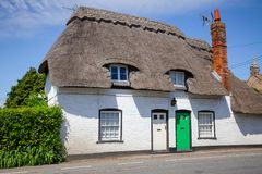Traditional white english thatched house in Southern England UK. A typical traditional English country thatched house or cottage with white walls in rural stock photos