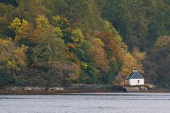 Traditional white house on scottish lake in highland Royalty Free Stock Images