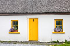 Traditional Irish house, Inisheer, Ireland. Traditional white stone house with thatched roof, yellow door and windows, Inis Oirr, Aran Island, Ireland Stock Photos