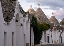Traditional white-washed conical-roofed houses in the Rione Monti area of the town of Alberobello in Puglia, south Italy. Traditional white-washed conical-roofed stock images