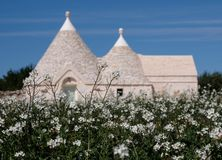 Traditional white-washed trulli house with conical roof, located outside the town of Locorotondo in the Itria Valley, Puglia Italy. Traditional white-washed royalty free stock image