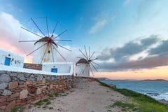 Traditional white windmills at sunrise, Mykonos, Greece stock photos