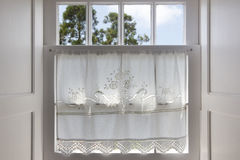 Traditional white wooden window with hand made curtain Stock Images