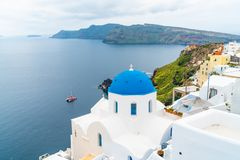 Whitewashed church with blue dome in Oia, Santorini. Traditional whitewashed church with blue dome in Oia with view of caldera and Aegean Sea. Santorini, Greece royalty free stock photography