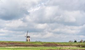 Wind mill in a typical Dutch rural landscape Stock Photos