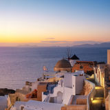 Traditional windmill and apartments in Oia, Santorini, Greece at Stock Images
