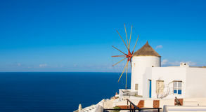 Traditional windmill and apartments in Oia village, Santorini, Stock Photo