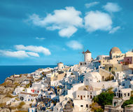 Traditional windmill and apartments in Oia village in Santorini Stock Image