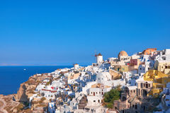 Traditional windmill and apartments in Oia village in Santorini Stock Photo
