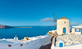 Traditional windmill and apartments in Oia village, Santorini, G Stock Images