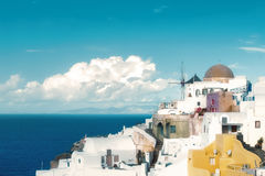 Traditional windmill and apartments in Oia village on a sunny d Stock Image